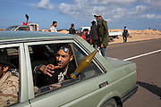 Libyan rebel fighters carry their weapons in civilian vehicles as they move towards the frontlines of a battle with pro-Qaddafi forces just outside the coastal town of Bin Jawwad. Rebels fought pro-Qaddafi forces there throughout the day as they tried to regain control the town from government forces that seized the town overnight.