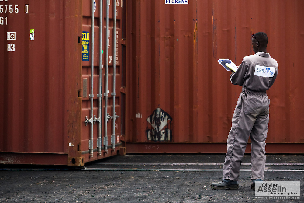 A worker flips through paperwork as he looks at containers at the sea port in Lome, Togo on Friday October 3, 2008.