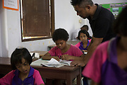 Joy is helped by the teacher during maths class.<br /> 2017 is the second year ever that Maniq children have attended school. Presently 12 children attend although not everyday as just reaching the school is a challenge in itself. <br /> <br /> The Maniq of Trang province differ slightly as they were the first to give up nomadic life and became permanently settled in their own remote forest village.<br /> <br /> Evidence suggests that the Maniq, a Negrito tribe of hunters and gatherers, have inhabited the Malay Peninsula for around 25,000 years. Today a population of approximately 350 maniq remain, marooned on a forest covered mountain range in Southern Thailand. Whilst some have left their traditional life forming small villages, the majority still live the way they have for millennia, moving around the forest following food sources. <br /> <br /> Quiet and reclusive they are little known even in Thailand itself but due to rapid deforestation they are finding it harder to survive on the forest alone and are slowly being forced to move to its peripheries closer to Thai communities.