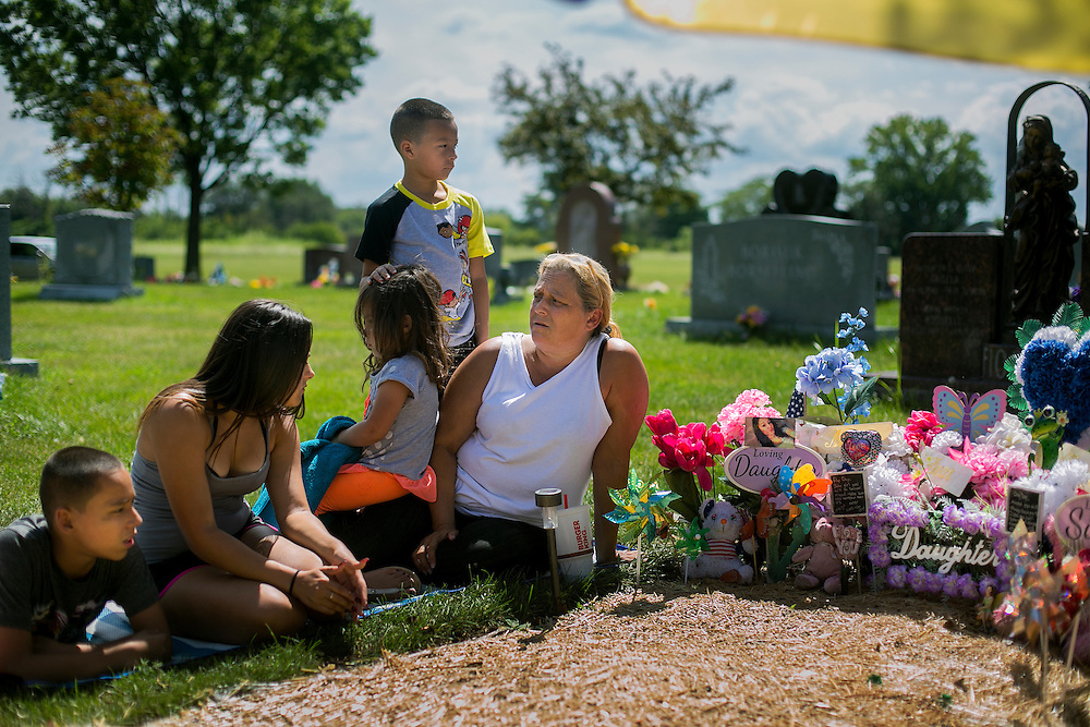 CHICAGO, IL - AUGUST 14, 2016: Diana Mercado sits with her daughter Miranda Mercado and several of her grandchildren at the gravesite of her daughter, Veronica Lopez, 15, who was shot and killed over Memorial Day weekend while riding in a car with friends. CREDIT: Sam Hodgson for The New York Times.