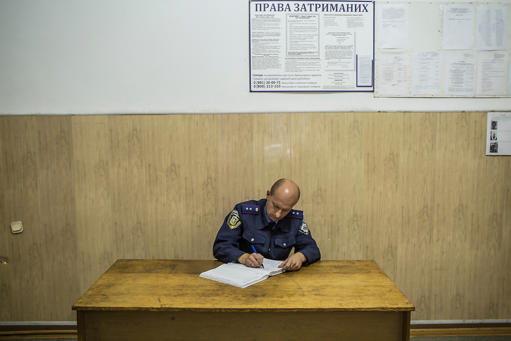 LVIV, UKRAINE - SEPTEMBER 16, 2015: A member of the old Lviv police force fills out paperwork connected to the arrest of Vladimir, 26, who was found intoxicated and sleeping in the city's central square and then swore at police officers in Lviv, Ukraine. In an effort to reform the notoriously corrupt Ukrainian police force, an entirely new force has been established in several cities, including Kiev and Lviv, with a primary focus on patrolling the streets. CREDIT: Brendan Hoffman for The New York Times