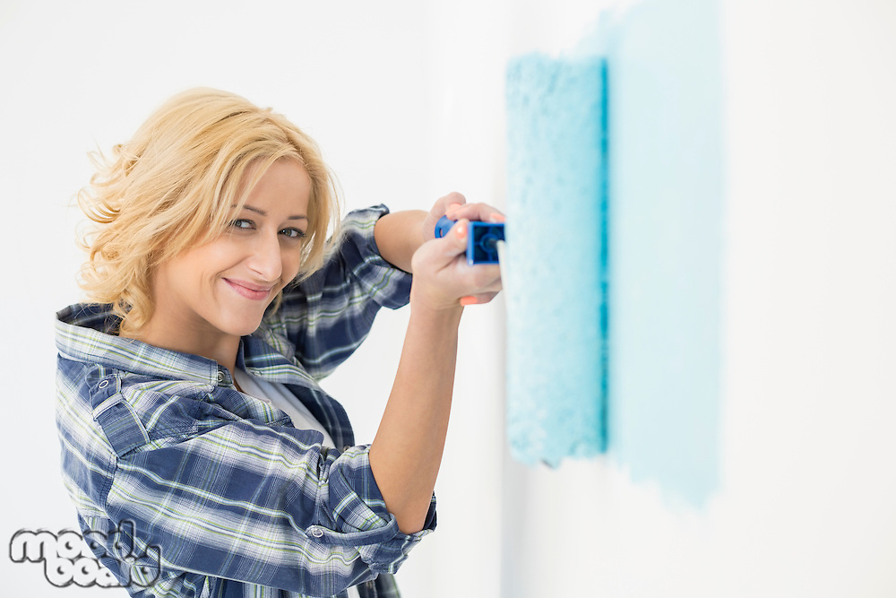 Portrait of beautiful woman painting wall with paint roller