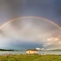 Full raibow over a church in the lake