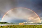 Full raibow over a church in the lake