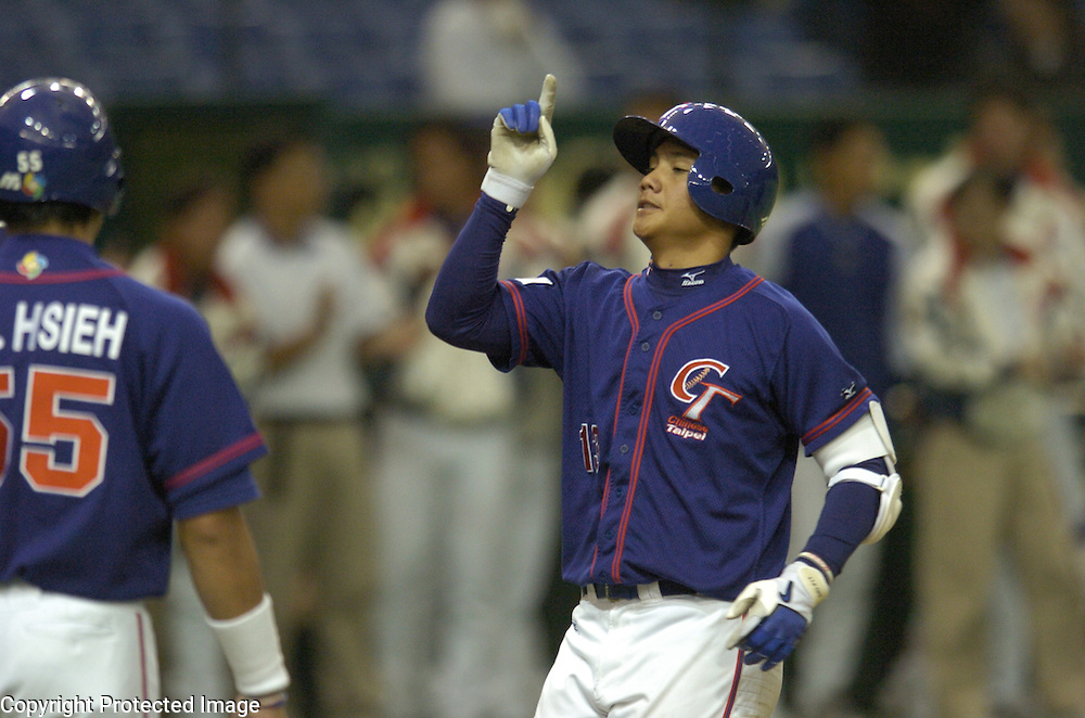 Team Chinese Taipei's Yung-Chi Chen points up after hitting a grand slam in the 4th inning against Team China in Game 5 of he World Baseball Classic at Tokyo Dome, Tokyo, Japan.