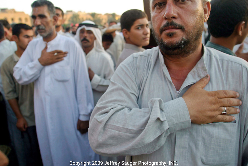 As an Shiite Iraqi man reads about Fatimah Al-Zahraa, the audience of Shiite repeat the passages out loud while performing Latim at the Imam Aba Al Fa Thill Abbas Holy Shrine in Karbala, Iraq, Thursday, July 24, 2003. Latim is hitting of oneself to share the pain and suffering of a significant holy person in Islam; men beat their chests and women hit their heads. The readings commemorated the death of Fatimah Al-Zahraa, the daughter of the Prophet Mohammad, wife of Imam Ali, and mother of Imam Aba Al Fa Thill Abbas and Imam Hussein. Karbala was built around the Imam Aba Al Fa Thill Abbas and Imam Hussein Holy Shrines as Shiite pilgrims have come to worship at the shrines since their deaths in 680 AD.