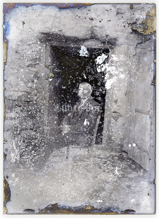 severely eroded glass plate with an adult man sitting in front of door