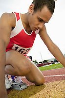 Young man in starting blocks
