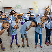 In Ein El-Hilweh refugee camp, home to 75.000 Palestinians. Girls sing and dance. It is summer break in the UNWRA school and Naba'a runs Play and Learn sessions in the empty school for vulnerable children. They aim is to give them a safe space to express themselves with out fear of repression. Developmental Action Without Borders(Naba'a) work in Palestinian refugee camps across Lebanon to help children in the camps.  The camps are densely over-crowded and many of the children are 4th generation refugees living in Lebanon with no citizenship or rights and under immense pressure. Naba'a is a mix of Palestinians and Lebanese and aim to give children a sense of security and freedom to express their needs and rights.Naba'a operates in communities governed by a multitude of political parties and religious groups and Naba'a keeps a strict independed line from any affiliation with any groups.