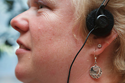 Woman with visual impairment using headphones.