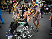 29 OCTOBER 2016 - BANGKOK, THAILAND: A Thai boy scout helps a man in a wheelchair go into the Grand Palace to pay homage to the late Thai King. Saturday was the first day Thais could pay homage to the funeral urn of the late Bhumibol Adulyadej, King of Thailand, at Dusit Maha Prasart Throne Hall in the Grand Palace. The Palace said 10,000 people per day would be issued free tickerts to enter the Throne Hall but by late Saturday morning more than 100,000 people were in line and the palace scrapped plans to require mourners to get the free tickets. Traditionally, Thai Kings lay in state in their urns, but King Bhumibol Adulyadej is breaking with tradition. His urn reportedly contains some of his hair, but the King is in a coffin,  not in the urn. The laying in state will continue until at least January 2017 but may be extended.       PHOTO BY JACK KURTZ