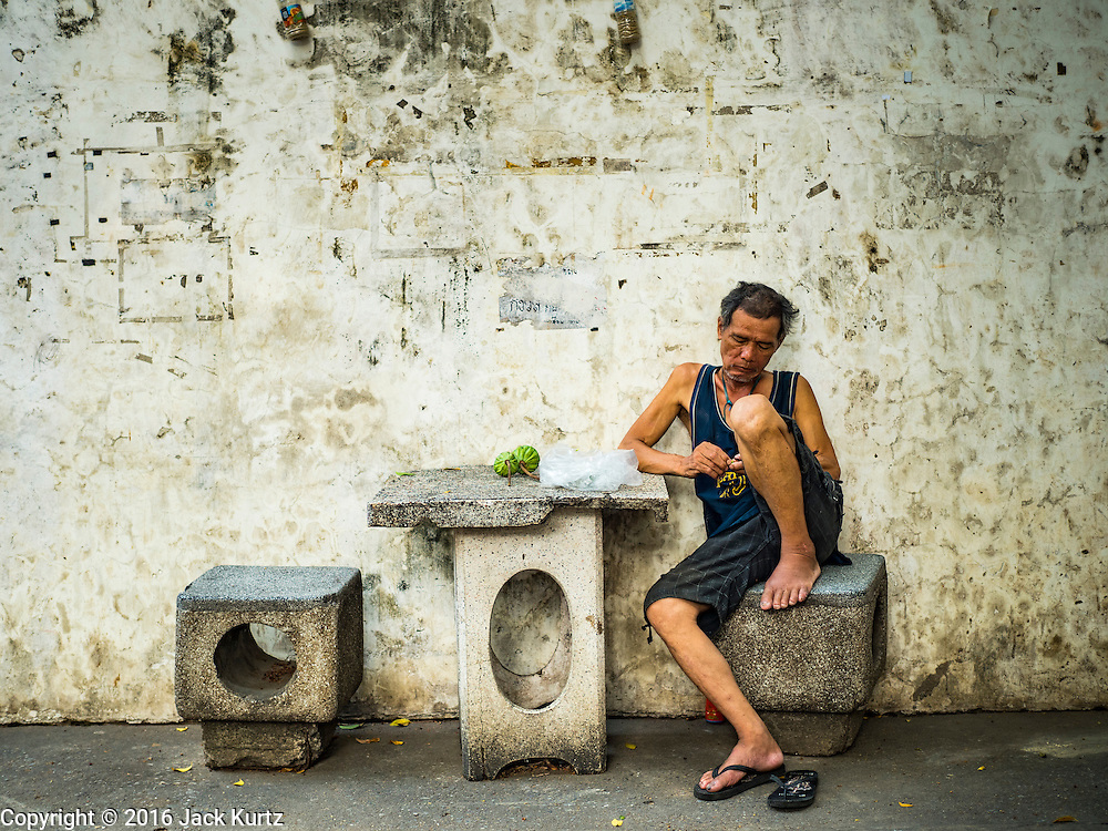 08 APRIL 2016 - BANGKOK, THAILAND:  A man eats a snack of lotus seeds in Mahakan Fort. The community is known for fireworks, fighting cocks and bird cages. Mahakan Fort was built in 1783 during the reign of Siamese King Rama I. It was one of 14 fortresses designed to protect Bangkok from foreign invaders, and only of two remaining, the others have been torn down. A community developed in the fort when people started building houses and moving into it during the reign of King Rama V (1868-1910). The land was expropriated by Bangkok city government in 1992, but the people living in the fort refused to move. In 2004 courts ruled against the residents and said the city could take the land. The final eviction notices were posted last week and the residents given until April 30 to move out. After that their homes, some of which are nearly 200 years old, will be destroyed.    PHOTO BY JACK KURTZ