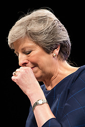 © Licensed to London News Pictures . 04/10/2017. Manchester, UK. Prime Minister THERESA MAY is handed a pill and coughs as she struggles with her voice whilst delivering her keynote speech on the fourth and final day of the Conservative Party Conference at the Manchester Central Convention Centre . Photo credit: Joel Goodman/LNP