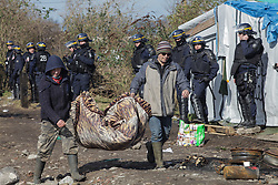 Licensed to London News Pictures. Calais, France. 03/03/16. Two volunteers carry bedding past a line of French riot police in the Calais 'Jungle'. French authorities are clearing the southern half of the Calais 'Jungle' camp, which charities estimate to contain 3,500 people.. Photo credit : Rob Pinney/LNP