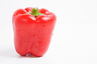 Close-up of fresh red bell pepper over white background