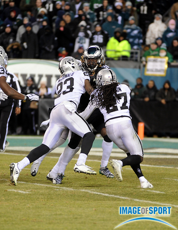 Dec 25, 2017; Philadelphia, PA, USA; Oakland Raiders defensive backs Reggie Nelson (27) and Dexter McDonald (23) make a stop of Eagles running back Jay Ajayi (36) during a NFL football game at Lincoln Financial Field. The Eagles defeated the Raiders 19-10. Photo by Reuben Canales