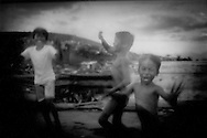 "Squatter boys run along side of taxi in front of the original Smoky Mountain landfill where rotting garbage would spontaneously catch fire and send up plumes of smoke in the Tondo slum of Manila, Philippines.  Families made a meagre living collecting, cleaning and selling recyclable materials.  Now families live in similar fashion at the ""New"" Smoky Mountain nearby."