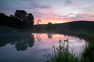 Reflections of sunrise in a still pond at Firefly Farm, Hauverville, New York, U.S.A.