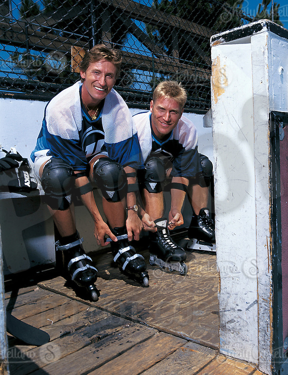 9 July 1996: NHL legend Wayne Gretzky straps on in-line roller hockey skates sitting next to retired player Brett Hull also wearing, custom gloves, stick and protective gear for a photo shoot with Ultra Wheels at an outdoor rink in Los Angeles, CA. EXCLUSIVE action photo of #99 playing rollerhockey out doors during the daytime. .