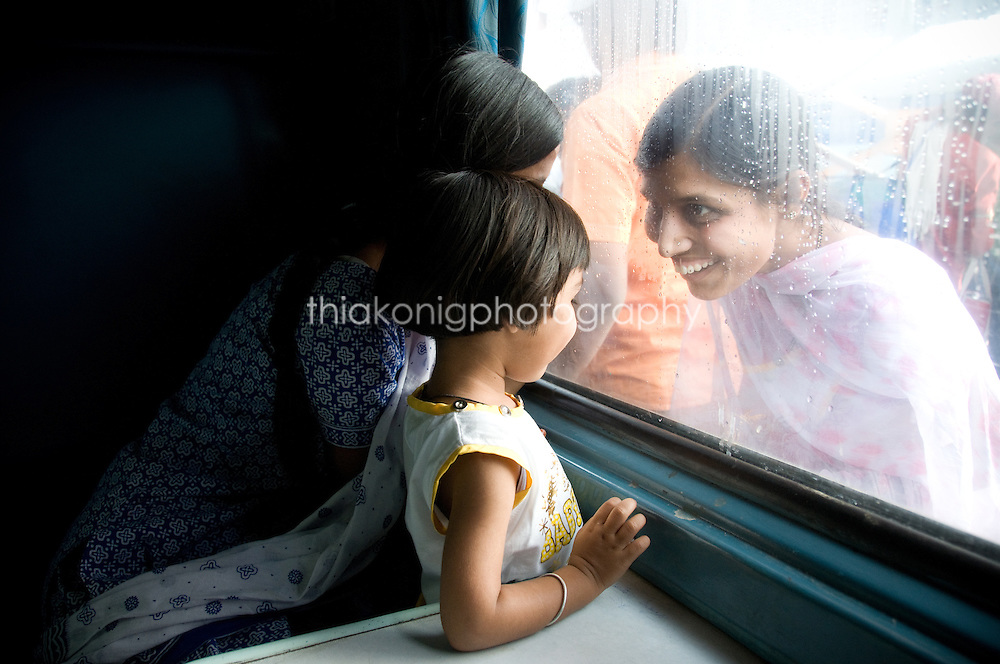 A waiting relative at a train station says hello to young girl inside train through window, India