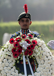 © Licensed to London News Pictures. 11/11/2012. Delhi, India. A member of the Indian Air Force holds a wreath with poppies during a Remembrance Day ceremony held at the Delhi War Cemetery, India, today. Remembrance Day (also known as Poppy Day or Armistice Day) is a memorial day observed in Commonwealth countries since the end of World War I to remember the members of their armed forces who have died in the line of duty. This day, or alternative dates, are also recognized as special days for war remembrances in many non-Commonwealth countries. Remembrance Day is observed on 11 November to recall the end of hostilities of World War I on that date in 1918.   Photo credit : Richard Isaac/LNP