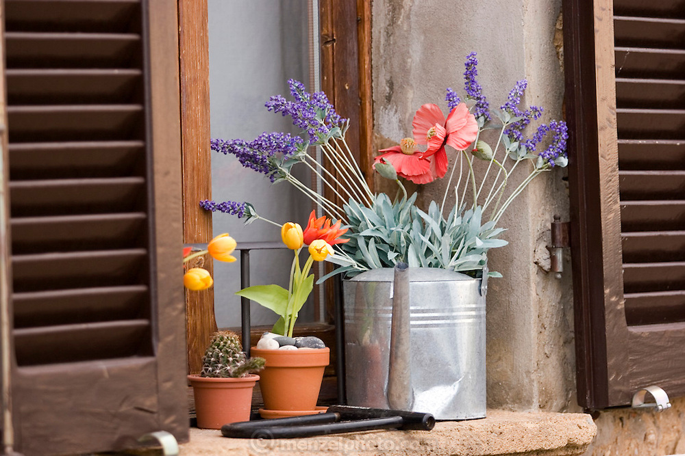 Bright flowers and a bike lock on a windowsill in Pienza, Italy. In 1996, UNESCO declared the town a World Heritage Site.