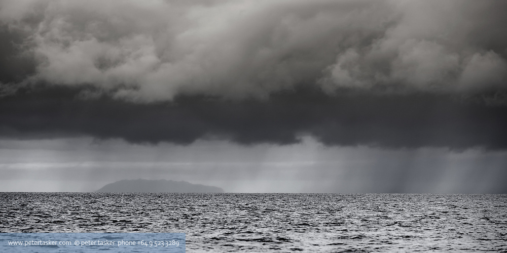 Little Barrier Island, as seen through rain while crossing the Firth of Thames, Hauraki Gulf, New Zealand.
