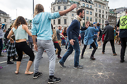 London, UK. 8 October, 2019. Climate activists from Extinction Rebellion dance as they block Trafalgar Square on the second day of International Rebellion protests to demand a government declaration of a climate and ecological emergency, a commitment to halting biodiversity loss and net zero carbon emissions by 2025 and for the government to create and be led by the decisions of a Citizens' Assembly on climate and ecological justice.