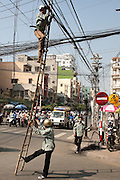 Men climbing a bamboo ladder to remove telephone lines in the middle of a traffic filled road, Ho Chi Minh City,Vietnam