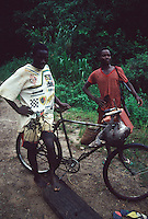 Local men carry an agouti on the handlebars of their bike. Eastern Democratic Republic of Congo (nee Zaire), central Africa