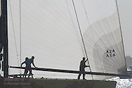 China Team crewmen wrestle spinnaker boom silhouetted by backlit spinnaker after long afternoon of America's Cup fleet racing; Valencia, Spain.