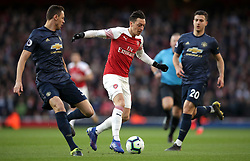 Arsenal's Mesut Ozil (centre) battles for the ball with Manchester United's Nemanja Matic (left) and Diogo Dalot during the Premier League match at the Emirates Stadium, London.