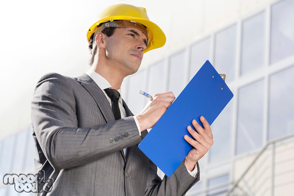 Young male architect writing on clipboard while looking away outside building