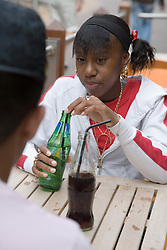 Teenage girl having a drink with a friend,