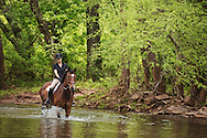 woman crossing a creek on horseback