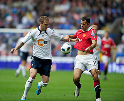 BOLTON, ENGLAND - Sunday, September 26, 2010: Manchester United's Ryan Giggs and Bolton Wanderers' Gretar Steinsson during the Premiership match at the Reebok Stadium. (Photo by David Rawcliffe/Propaganda)