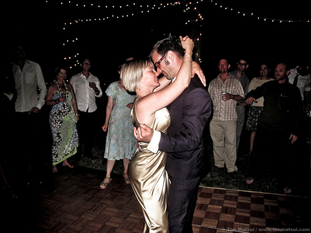 A newlywed couple dances at their wedding at night.