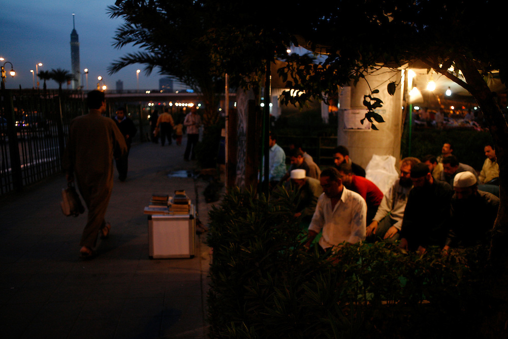 Men pray near Tahrir Square at night, the Cairo Tower is seen in the background.
