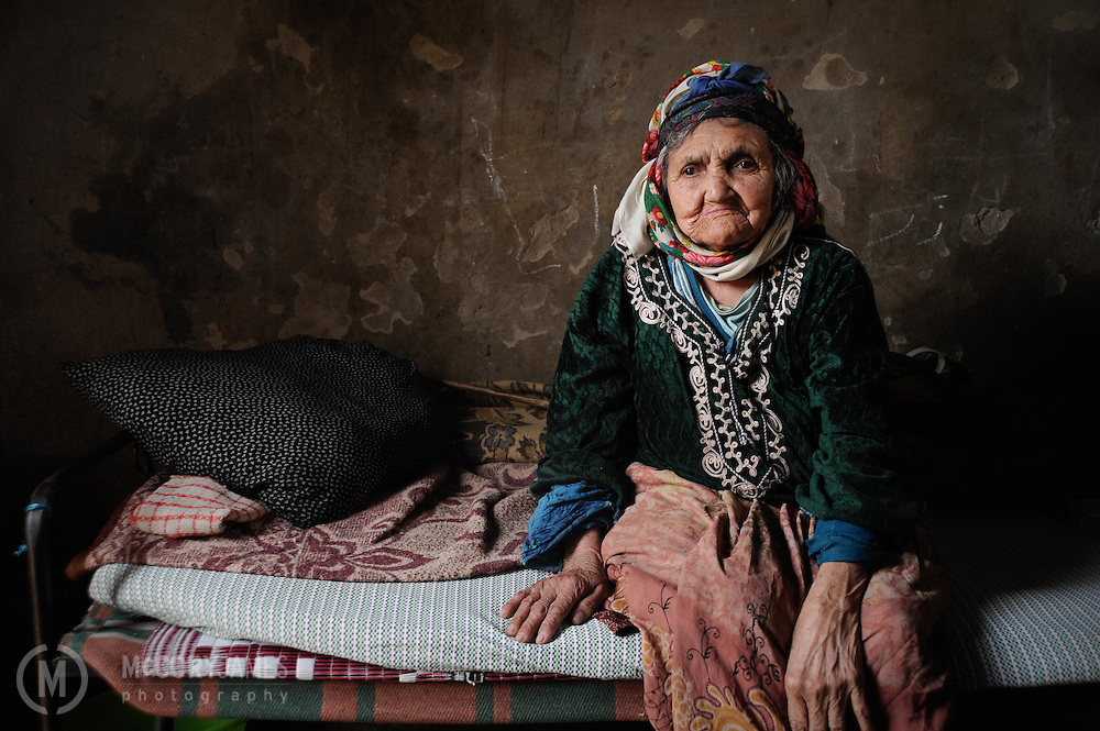 An elderly Tunisian woman sits on her bed inside her home