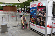 A tired elderly visitor to the capital yawns next to the Information kiosk at the London Eye, on 20th July 2017, on the Southbank, London, England.