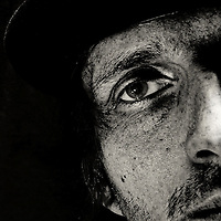 cropped portrait of a man with hat starring into the camera