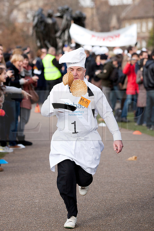 © Licensed to London News Pictures. 21/02/2012. LONDON, UK. Labour MP Stephen Pound tosses two pancakes as he flaunts the rules during a pancake race outside the Houses of Parliament today (21/02/12). Lords, Members of Parliament and political journalists today took part in the 2012 'Rehab Parliamentary Pancake Race' in aid of disability charity Rehab. The parliamentary team took the trophy after an extra lap was run due to widespread cheating. Photo credit: Matt Cetti-Roberts/LNP
