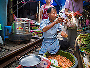 27 SEPTEMBER 2016 - BANGKOK, THAILAND: A man sells grilled shrimp in the market in the Samut Songkhram train station. The train from Baen Laem to Samut Songkhram (Mae Khlong) recently resumed service. The 33 kilometer track was closed for repair for almost a year. In Samut Songkhram, the train passes over the market. Vendors pull their stands out of the way and people step out of the way as the train passes through the market. It is one of the most famous train stations in Thailand and has become an important tourist attraction in the community.      PHOTO BY JACK KURTZ