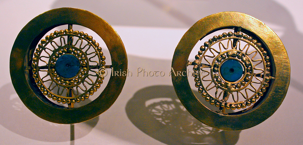 Pair of Earflares.Peru : Sican (Lambayeque) 9-11th century.  Hammered gold, turquoise inlay.  Archaeologists recently excavated a temple platform, where, almost forty feet below they found the tomb of a mighty Sican lord laid to rest with all the trappings of his power and wealth.