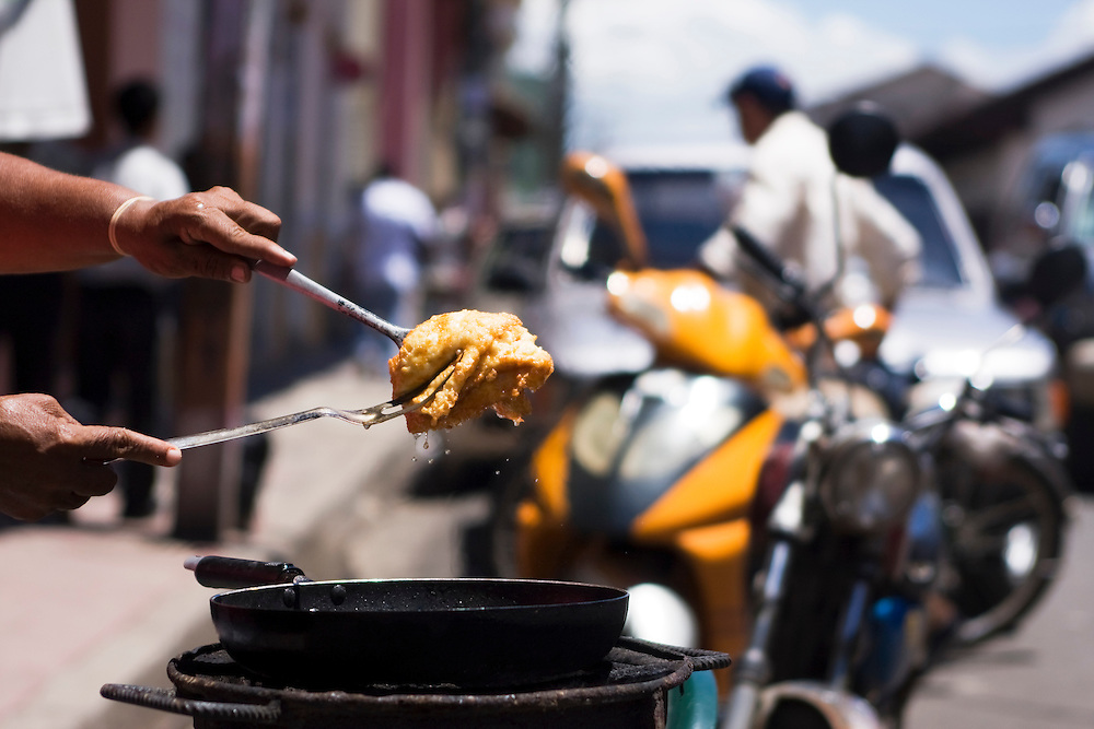 A woman cooking at a street stall. She is cooking fried cheese bubbling and cooking in a pan on the side walk in Granada, Nicaragua. Granada is Nicaragua's most famous city. founded in 1524 it is one of best examples of Spanish colonial architecture in the Americas. .it has a varied history including its almost total destruction by filibuster William Walker in a childlike tantrum. Today it is a popular tourist town though retains a strong sense of its own identity.