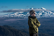 Matthew on the tops of Kaimanawa ranges with Mt Ruapehu in the background.