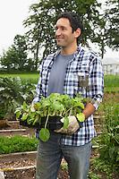 Man carrying plants in field