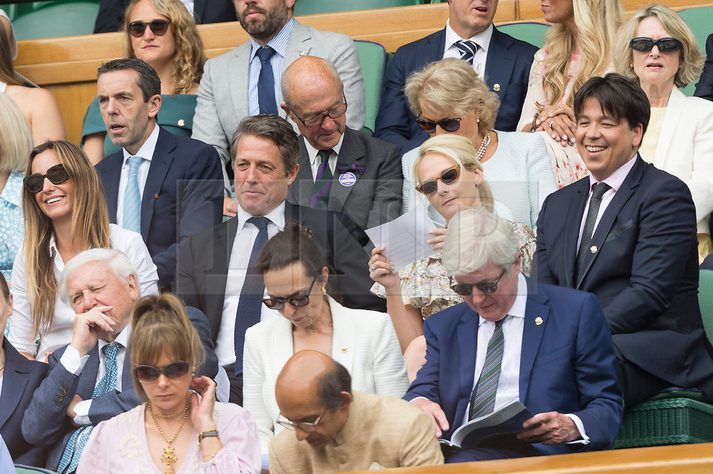 © Licensed to London News Pictures. 12/07/2019. London, UK. Anna Grant, Hugh Grant, Kitty McIntyre and Michael McIntyre watch centre court tennis in the royal box on Day 11 of the Wimbledon Tennis Championships 2019 held at the All England Lawn Tennis and Croquet Club. Photo credit: Ray Tang/LNP