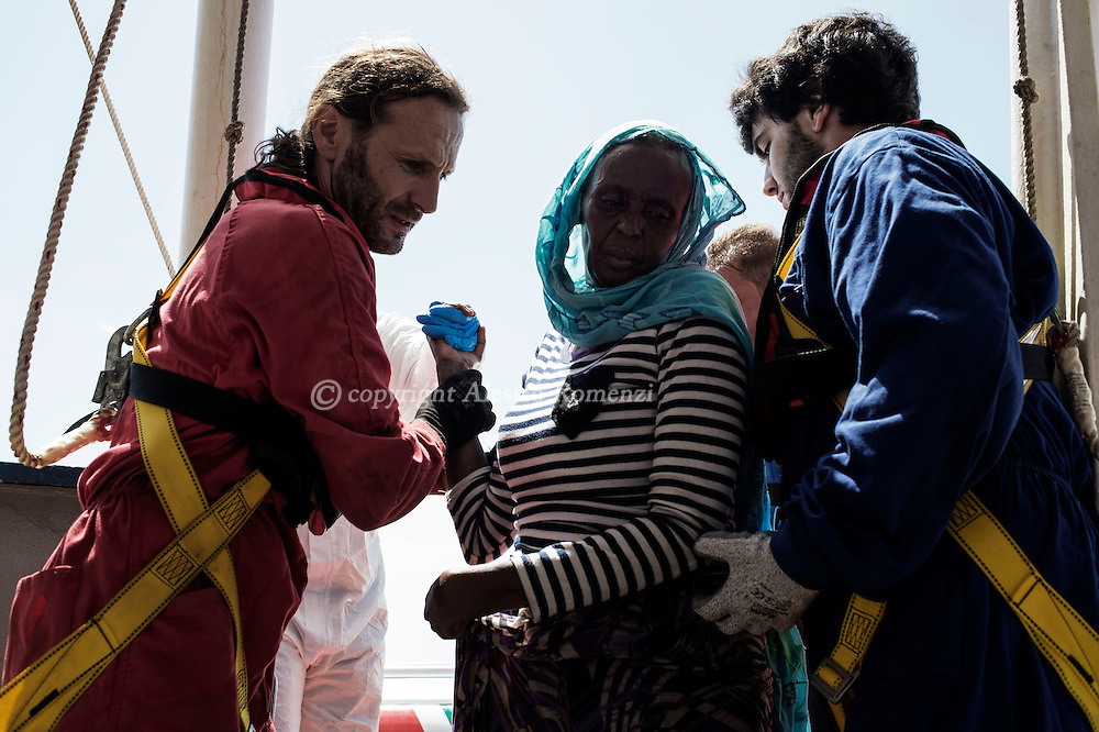 Italy: MSF Dignity1: An African woman rescued at the sea is helped to get on the Dignity1 on August 23, 2015. Alessio Romenzi