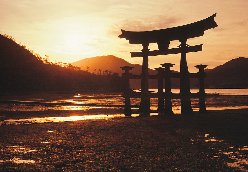 The torii gate at Itsukushima Shrine on Miyajima Island, Hiroshima, Honshu, Japan, is silhouetted by the evening sun.